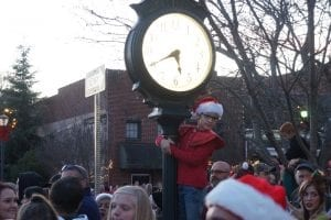 Crowd size sends one child up the clock downtown in an attempt to see the nights events.
