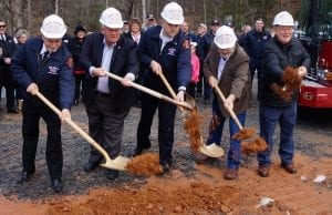 Officials turn the first shovel of dirt in the groundbreaking ceremony for Cherry Log's Fire Station.