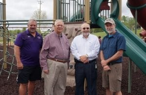 Left to right, Kevan White, David Ralston, Charlie Paris, and Travis Crouch take a moment to pose in front of the county's new playground.